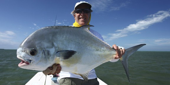 Frank Smith of 12Wt apparel holds up a monster October permit he caught on fly.