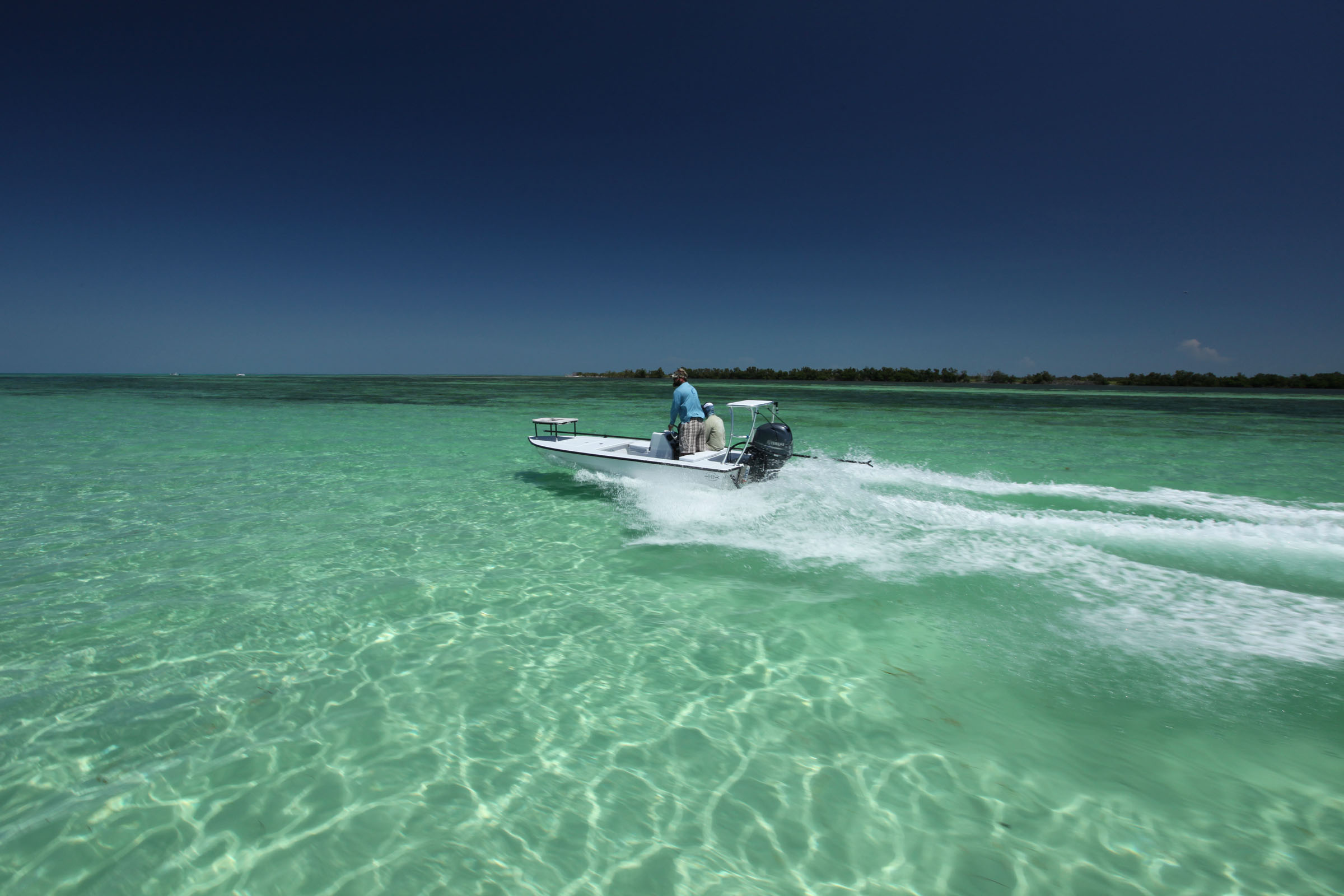 Bryan Bear Holeman rides over clear oceanside sand flats in pursuit of Tarpon on fly